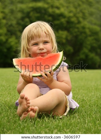 adorable little toddler sitting on the grass with a piece of watermelon - stock photo