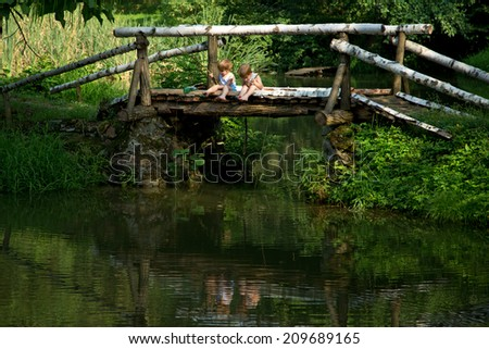 Adorable Little Twin Brothers Sitting on the Edge of Wooden Bridge and Fishing on Beautiful Lake at Summer - stock photo