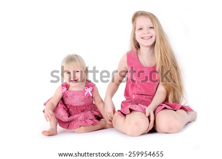 adorable little two sisters 9 year and  1  year old on white background - stock photo