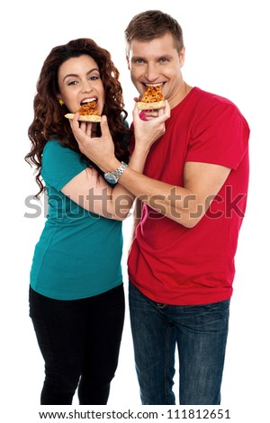 Adorable love couple enjoying pizza pie together. Both making each other enjoy pizza piece - stock photo
