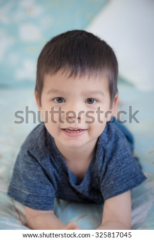 Adorable mixed race Asian Caucasian 2 year old boy lays in a cute pose on a bed inside his home - stock photo