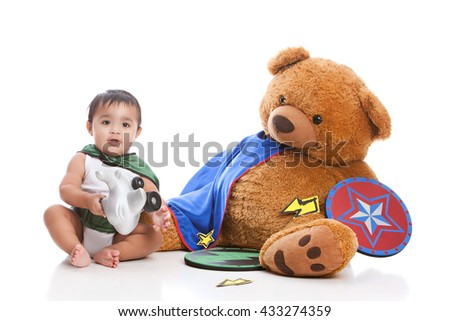 Adorable, mixed race baby boy wearing a cape and sitting next to a giant, stuffed bear wearing a cape and holding a shield.  Isolated on white.