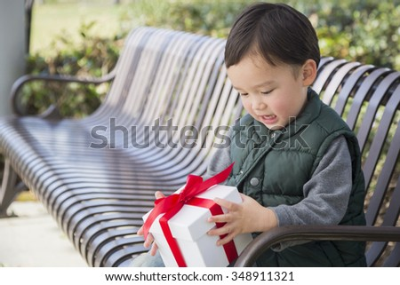 Adorable Mixed Race Boy Opening A Christmas Gift Outdoors On A Bench. - stock photo