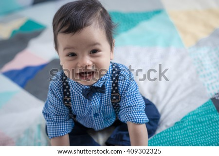 Adorable mixed race 11 month old Asian Caucasian boy plays cheerfully on a colorful geometrically shaped bed cover. Natural indoor lighting. - stock photo