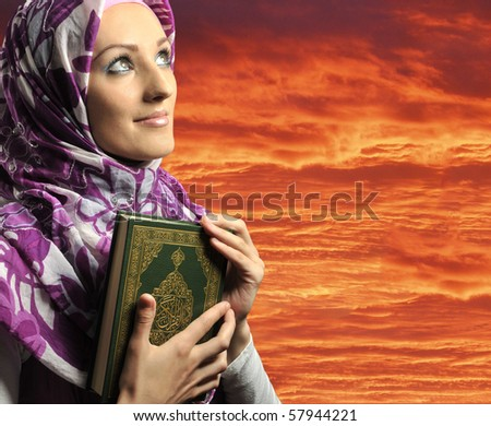Adorable Muslim girl holding holy book Koran, against red sky - stock photo