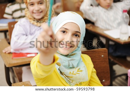 Adorable Muslim girl in classroom with her friends children students - stock photo