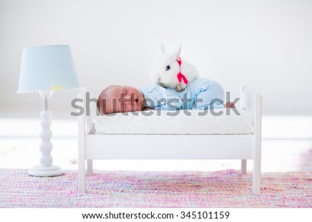 Adorable new born kid sleeping in a white toy bed with real rabbit. Nursery for newborn baby. Cute boy taking a nap in sunny bedroom with his bunny. Family with children and pets. Child and animal. - stock photo