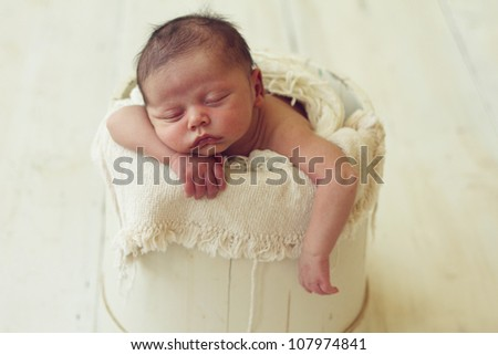 Adorable newborn baby boy in a bucket - stock photo