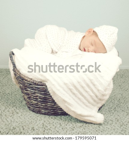 Adorable newborn baby child sleeping in pajamas in a wicker. Tone effect.  - stock photo