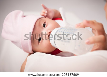 adorable newborn baby girl drinking from bottle with help of mother - stock photo