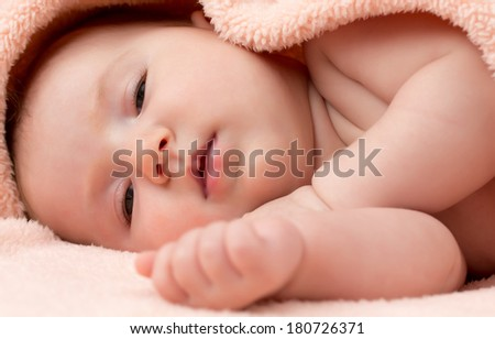 Adorable newborn baby girl lying in bed