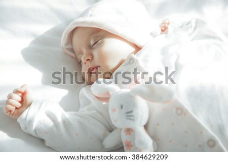 Adorable Newborn baby peacefully sleeping with her toy. Closeup Portrait. Studio shot, Horizontal - stock photo