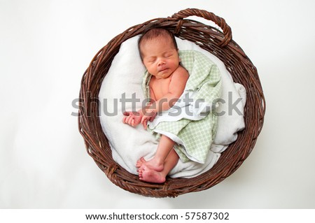 Adorable newborn baby resting in a wicker basket - stock photo