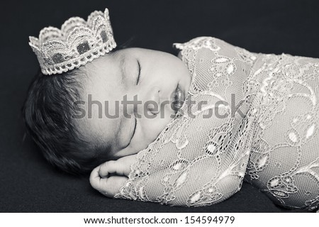 Adorable newborn baby sleeping wrapped on pink lace on brown cushion with a crown on the head. - stock photo