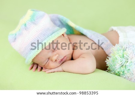 adorable newborn baby with funny cap on her head sleeping on stomach - stock photo