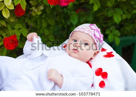 Adorable newborn girl in roses garden - stock photo