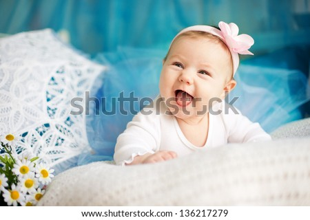 Adorable newborn girl laughing on white plaid with flower on head and blue ballerina skirt - stock photo