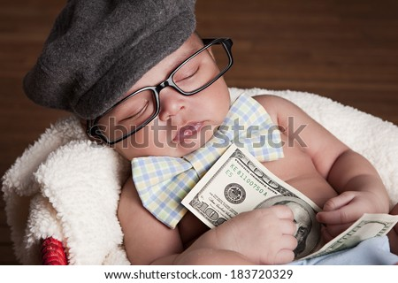 Adorable newborn wearing a hat, bow-tie and glasses and holding a hundred dollar bill.