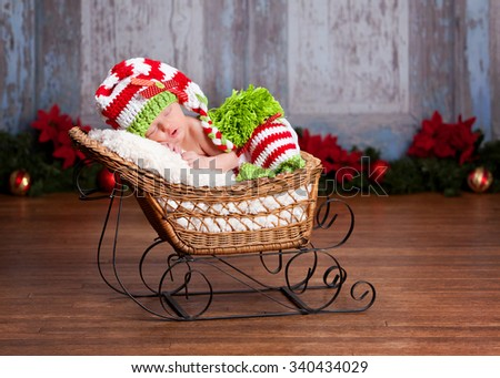Adorable newborn wearing a red, white and green striped hat and leggings - fast asleep in a little sled.  Christmas decor in the background.  Room for your text. - stock photo