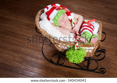 Adorable newborn wearing a red, white and green striped hat and leggings - fast asleep in a little sled.  Room for your text. - stock photo