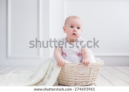 adorable nice baby portrait sitting in basket with blanket on white background