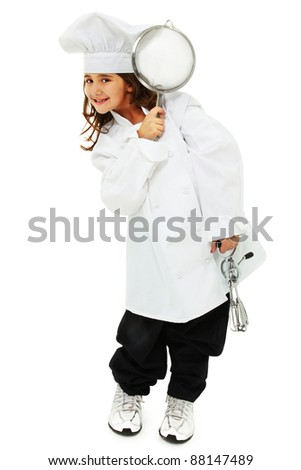 Adorable nine year old girl standing in baggy chef uniform over white with egg beater and skimmer. - stock photo