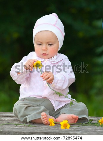 Adorable one-year baby sitting on the table with flowers - stock photo