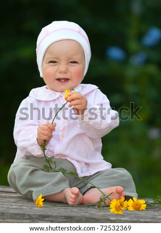 Adorable one-year baby sitting on the table with flowers and smiling - stock photo