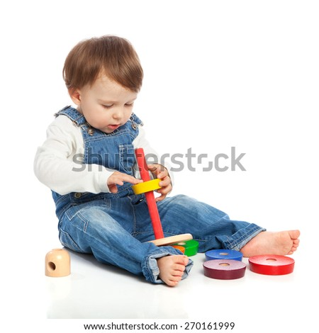 Adorable one year old child playing with color rings, isolated on white - stock photo