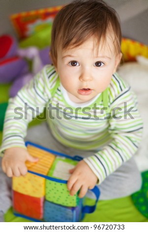 Adorable one year old child playing with toy cubes - stock photo