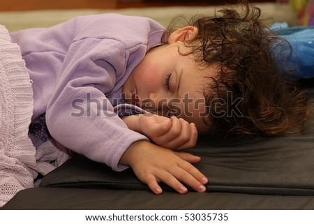 Adorable portrait of kid sleeping on black mattress - stock photo