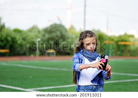 Adorable pre-teen tweenie kid girl making self portrait with funny duck face on her cell phone on the school soccer field - stock photo