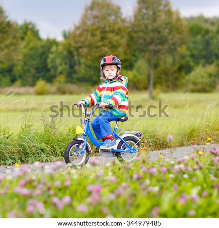 Adorable preschool boy riding on bike on warm autumn day. Countryside. Child in helmet. Active leisure and sports for kids. - stock photo