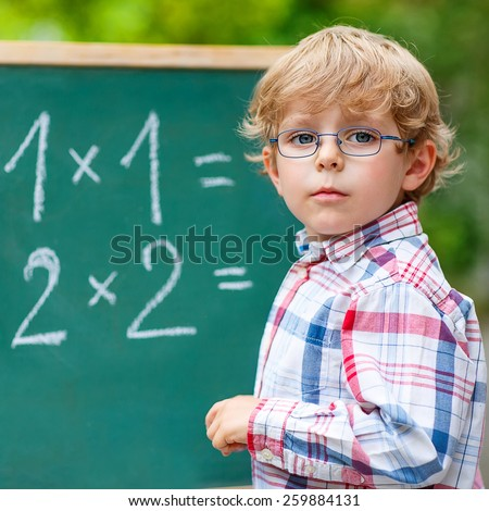 Adorable preschool kid boy with glasses at blackboard practicing mathematics, outdoor. school or nursery. Back to school concept
