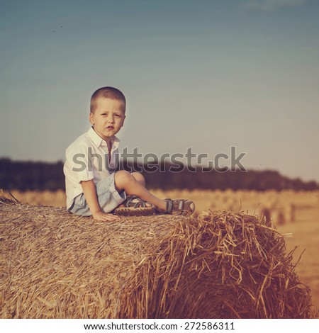 Adorable preschooler boy sitting on a haystack in wheat field on warm and sunny summer day.Toned image. - stock photo