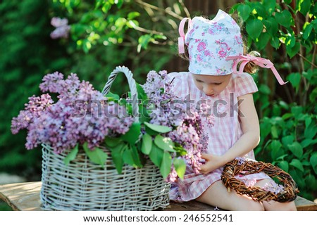 adorable preschooler girl in pink dress and floral headband making lilac wreath in spring garden - stock photo