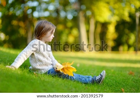 Adorable preschooler girl sitting on a green grass and holding yellow maple leaves on beautiful autumn day - stock photo