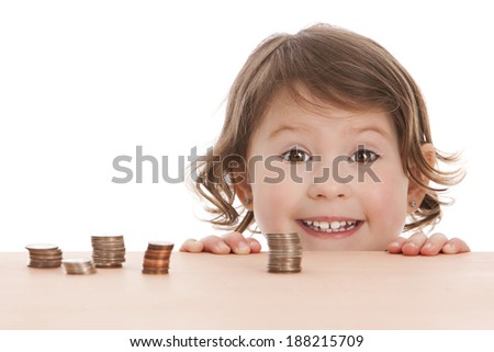 Adorable preschooler peeking over a table with stacks of coins on it.  Isolated on white with room for your text.  - stock photo