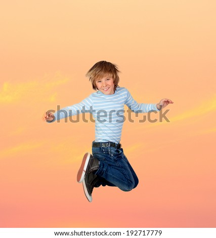 Adorable preteen boy jumping with a orange sky of background - stock photo