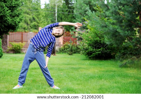 Adorable preteen girl doing exercise outdoors on the lawn - stock photo