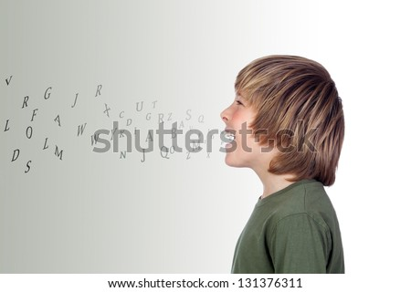 Adorable preteen with many letters out of his mouth isolated on a over grey background - stock photo