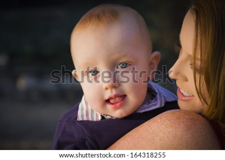Adorable Red Head Infant Boy Portrait with His Mother Outdoors in Dramatic Lighting.