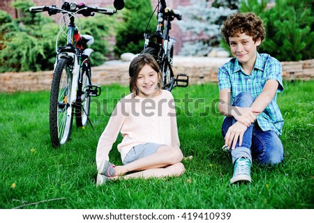 Adorable school aged boy and girl in the garden with bikes - stock photo