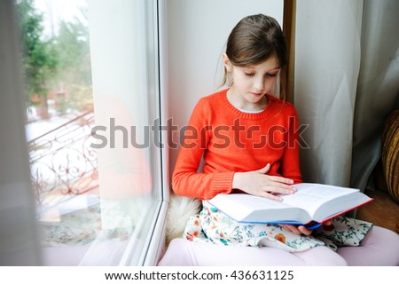Adorable school aged brunette kid girl in orange sweater sitting by the window and reading book - stock photo