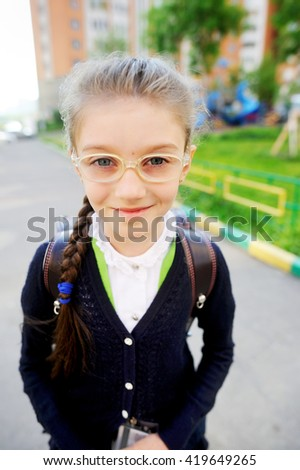 Adorable school aged  girl with backpack outdoor in the park - stock photo