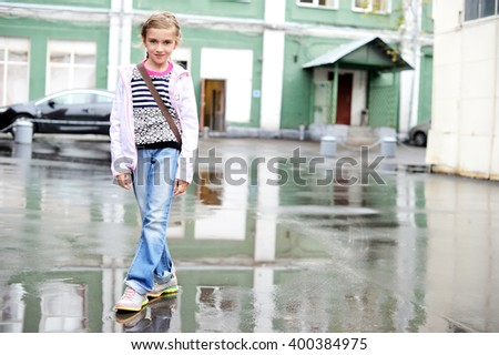 Adorable, school aged kid  girl in jeans and white jacket  walking in the city street in rainy day - stock photo