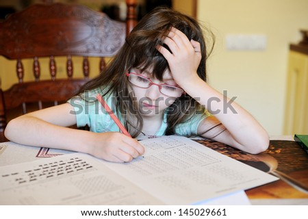 Adorable school girl doing her mathematics homework - stock photo
