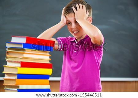 Adorable schoolboy with stack of books in classroom - stock photo