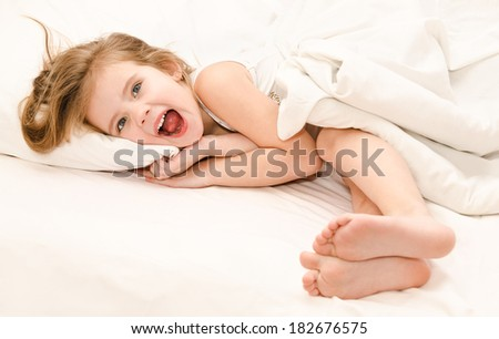Adorable screaming little girl waked up in her bed  - stock photo