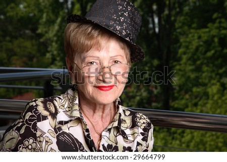 Adorable senior woman wearing glasses, a hat and lovely red lipstick. Lovely attitude. Outdoor. - stock photo